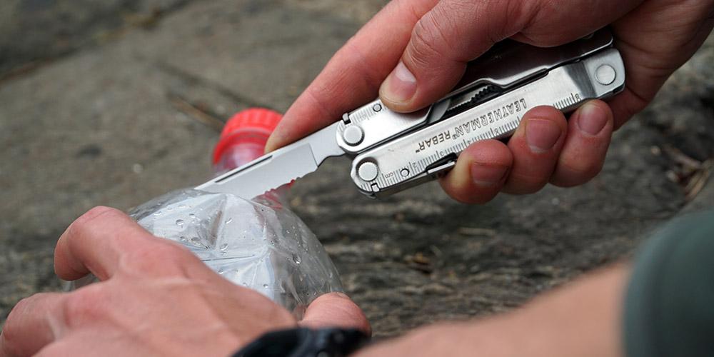 Серрейторный нож мультитула Leatherman Rebar разрезает пластиковую бутылку